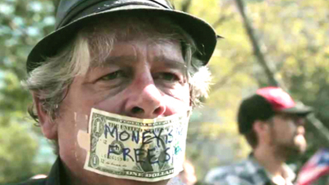 man with money over his mouth