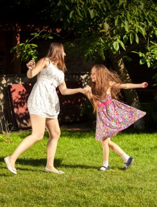 brunette woman an young girl holding ands and dancing at yard