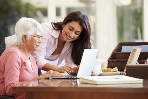 young woman helping older woman with computer